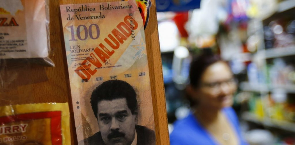 """A sample bank note with the face of President Nicolas Maduro and the word """"devaluated"""" is seen at a market in Caracas February 13, 2015. Venezuela on Thursday unveiled a devaluation of 69 percent at the opening of a new free-floating currency exchange rate system, part of President Maduro's efforts to shore up the OPEC nation's coffers amid tumbling crude prices. The move may help ease market concerns of a possible debt default and boost supplies of dollars to a currency-starved economy, but risks spurring inflation amid recession, product shortages and swelling supermarket lines. REUTERS/Jorge Silva (VENEZUELA - Tags: POLITICS BUSINESS) - RTR4PH3V"""